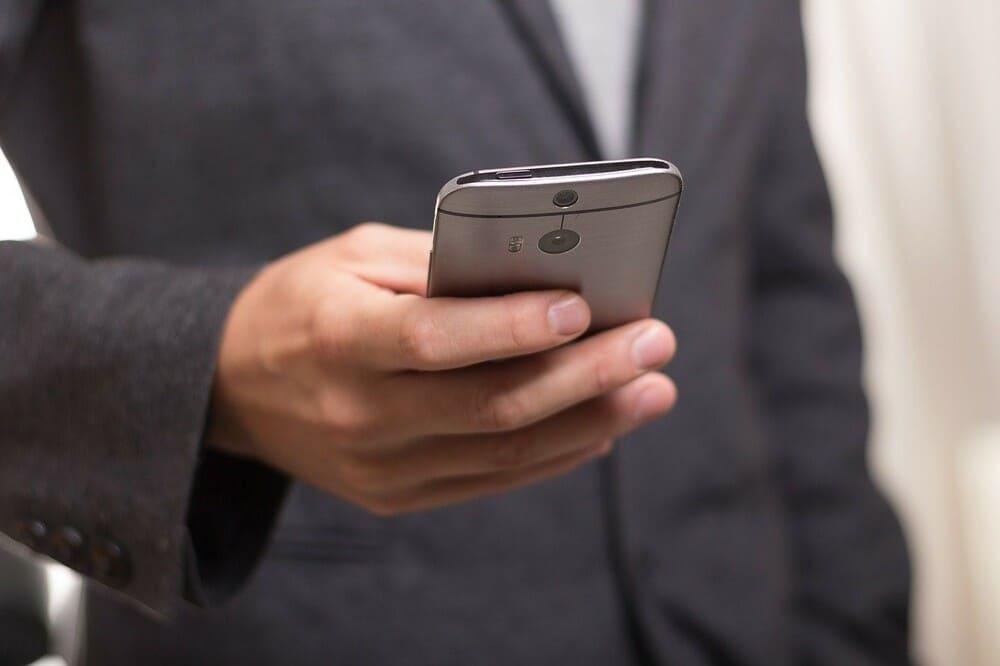Person hält Smartphone in der Hand - Online Casino mit Handy bezahlen