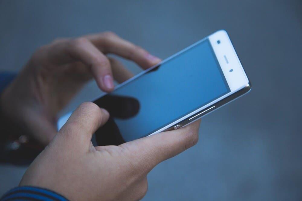 Person hält Smartphone in den Händen - Online Casino Vergleich